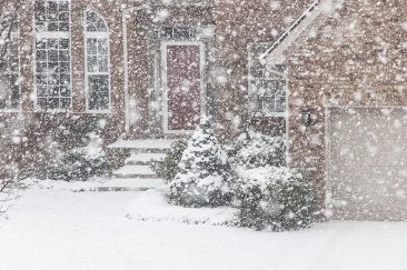 Winter storm and snow covering a home