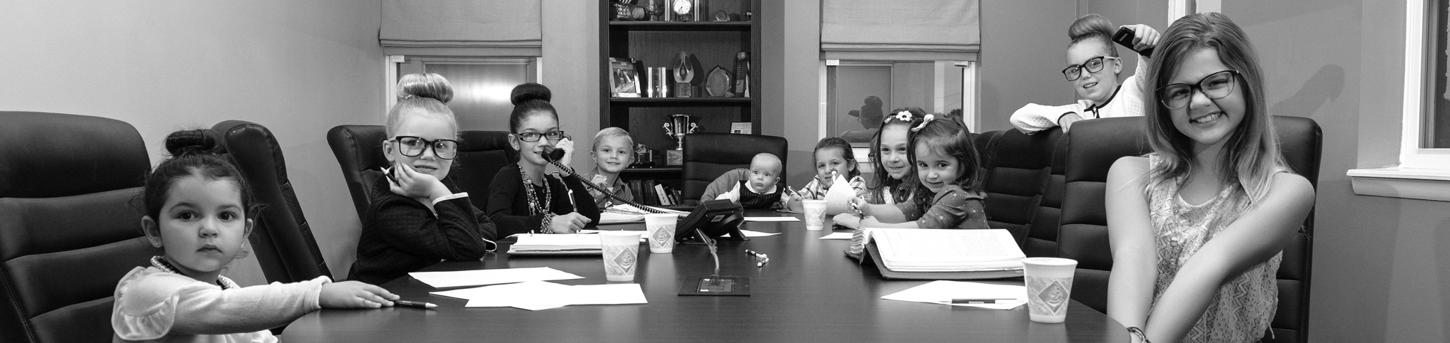 The future generations of Hanson & Ryan sitting around a conference room table.