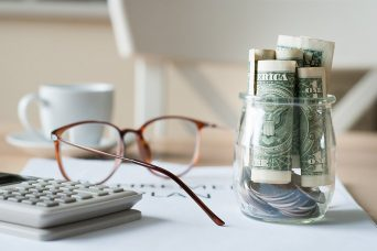Calculating bills with calculator, glasses and money in a jar