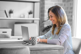 Woman types and smiles at laptop